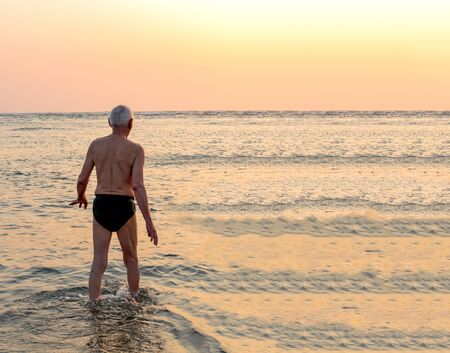 Old Aged Elderly male with healthy physique, wearing underpants, is enjoying his post retirement life on beach vacation, and is excited to take bath in sea/ocean during golden hours of sunrise/sunset.