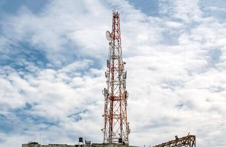 Tall Mobile Phone Tower, Celluar Tower with umbrella dish, attenuators, amplifiers and repeaters, installed on rooftop and is rising high in the Sky with Dramatic Sky background on a sunny noon. -