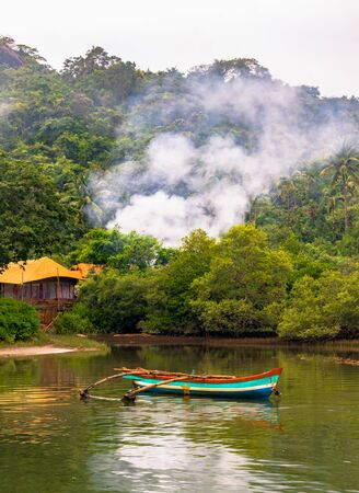 Mesmerizing tropical landscape of remote coastal area comprising mangrove forest with hill and clouds, a temporary cottage for fishing enthusiasts and a wooden canoe for rowing and fishing in the pond