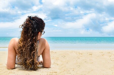 Back view pose of attractive and beautiful young girl in her early 20s with long and colored curly hairs, while getting tanned at beach on a bright sunny day, during her holidays on tropical island.