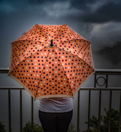 Amazing photo of rainy season of monsoons, wherein an unrecognizable teenage girl is holding a peach colored umbrella with polka dots design, while standing on a  cliff edge, enjoying the clouds.