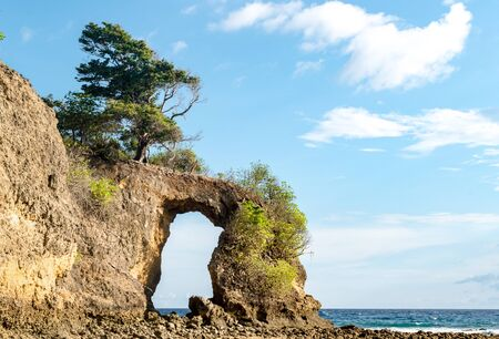 Geological formation known as Rock Arch at Neil island, looks like natural bridge or a natural gate, formed off constant erosion; with calm sea and clear blue sky in background with visible horizon.