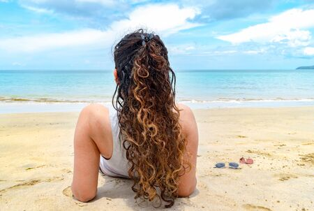 Back view pose of attractive female model enjoying her holidays at an exotic beach. The photo focus on her beautiful hairstyle with colored curly hair and flawless skin getting sun tanned on sunny day
