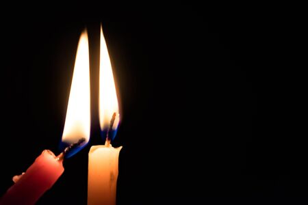 Two Candles of different colors lighting flames of each other, with dark black background. -Image. Imagens