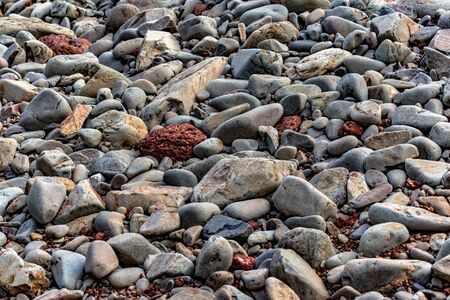 Smooth and Colorful beach Rocks/stones. Geographically formed off volcanic activities, are lying alongside beach. They appear smooth, as they are constantly being weathered by oceanic waves. - Image. Imagens