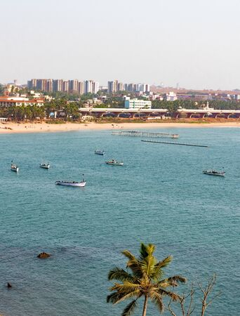 Beautiful vertical photo of seascape comprising calm blue ocean, a natural beach, fishing boats, palm tree, economically developed city, Skyscrapers, bridge. The Beach is leisure point of residents.