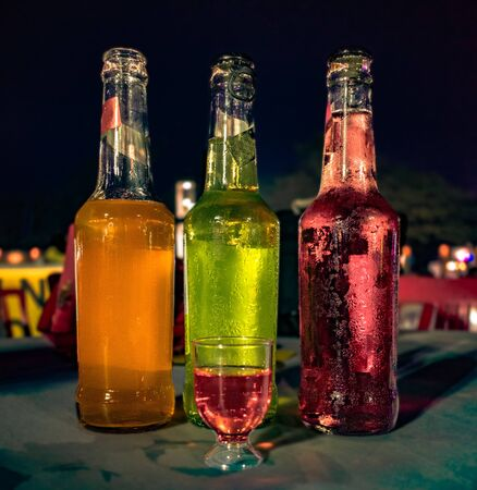 Three bottles of different colored Wines placed adjacent to each other with a small glass filled with red wine for tasting at a Wine Tasting Festival. Imagens