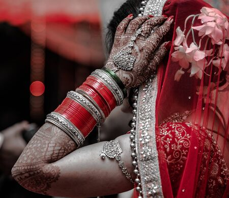 Beautiful Indian Bride in traditional hindu wedding attire with lehnga, bridal bangles and shy pose