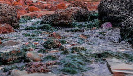 Vigorous fast flowing stream of fresh water river, cutting through algae rich rocks, giving the water a colorful tone. Zdjęcie Seryjne - 143085394