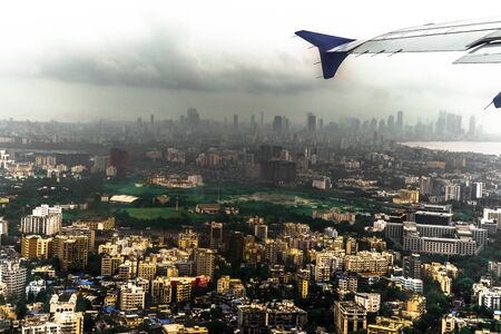 Aerial view of a metropolitan city from window side of a plane in a rainy season with visible rain in far area