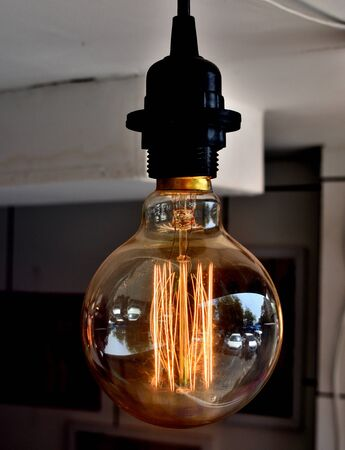 Glowing hot filament of tungsten in Edison Light Bulb, glowing dim in daylight being used for interior decoration. Imagens