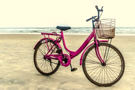 Pink colored ladies bicycle iconic at the time of 90s parked in the isolation at the beach. Many Childhood memories as this is the first type of personal vehicle for transportation for many of us. Imagens