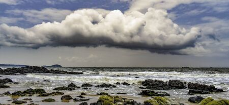 Very beautiful and panoramic landscape or seascape with dramatic cumulus clouds, stormy and blackish in  color, in blue sky, about to rain in rainy season on beach with waves and black algae rich rock