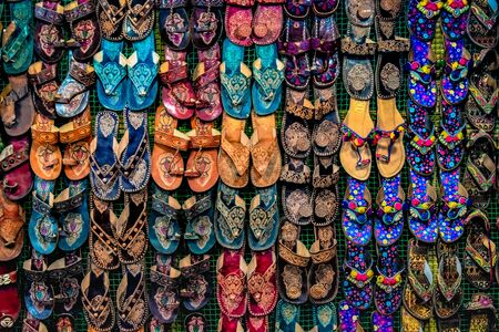 Kolhapuri Chappal- Colorful and variety of Ladies Ethnic Footwear displayed on sale at the street market in India. Kolhapuri Chappal in India are usually wore with Ethnic wear of Indian Culture.