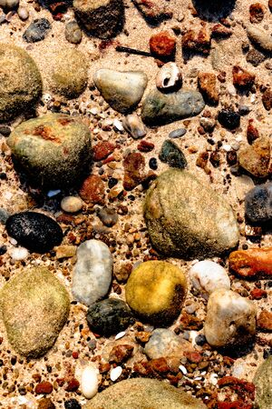 Beautiful and colorful stones, sea shells and geological rocks, containing minerals of sea, lying underwater on the sea floor in the shallow waters of a beach, appearing more vibrant in sunlight Imagens
