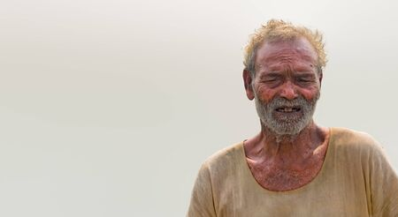 Portrait of poverty stricken Old Aged Male of South Asian origin in his late 70s, posing in dubious mood. Belongs to labour class, is tired and wearing pale and dirty stinky clothes, have white beard Stock fotó