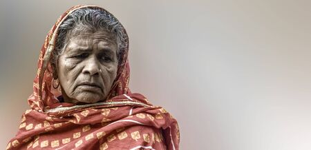 Beautiful portrait of an Indian Origin elderly woman, having wrinkles on her face and white & grey hair, wearing red saree with veil, thinking in sorrow. Plane background space for tagline/advertising