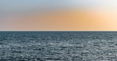 Beautiful view of high seas, in calm ocean, after sunset, showing perfect blend of warm colors, due to dispersion of light in sky. Clear visible horizon giving impression as if the earth is flat.