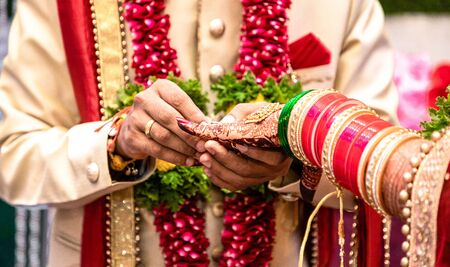 Engagement Ring ceremony- Indian Hindu male putting ring on bride's decorated finger. Couple is well attired as per traditional Indian Hindu wedding. Groom wearing Jodhpuri suit and floral garland. Imagens