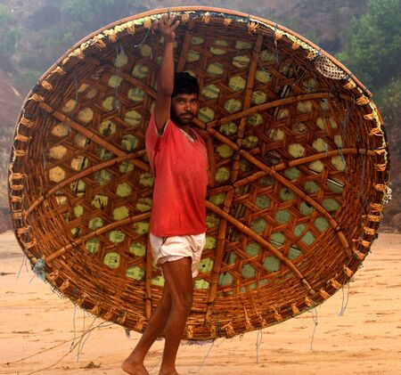 Healthy but poverty stricken, nomadic fisherman of south indian origin lifting the hand made coracle boat after his fishing shift. Satisfied with the day work and posing in a happy mood to the camera.