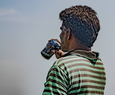 Middle aged male of south asian origin with white beard and rough, dry, messy hair, wearing striped tshirt looking towards horizon and quenching his thrust by enjoying cold drink/beer in a sunny day.