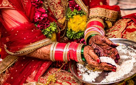Indian Hindu Bride wearing beautiful Red Lehenga in her marriage, and performing traditional ritual offering rice to God with both her hands, hands are decorated with colorful bangles and henna mehndi