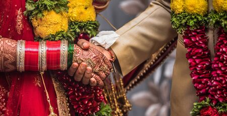Indian Hindu couple wearing traditional Indian dress and floral garland, holding each other hands during their marriage promising blissful life. Beautiful Henna Mehndi art and bangles on birde hands Imagens - 144239843