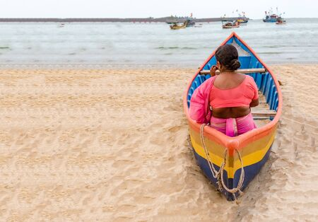 Middle Aged South Indian Woman, wearing Ethnic Saree draped in Marathi style, waiting in colorful small canoe boat, for her husband to return from fishing in evening. Space in left for writing texts. Banque d'images