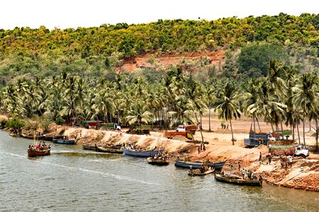 Coastal village of Southern Indian subcontinent, with plenty of palm trees alongside a river bank, where laborers are mining the sand from floodplains in their small boats, and loading it in truck. Imagens - 144239848
