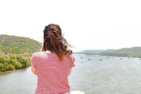 Beautiful, Trendy and Young Female Brunette. A Tourist/Travel blogger/storyteller taking scenic photograph, during solo trip cum exploration of world Imagens - 144239850