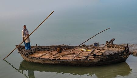 Middle Aged Indian Man rowing his wooden boat alone, towards river Ganges bank, in freezing winters of North India. Visibility is very low due to fog in winters. He is wearing kurta, lungi and muffler