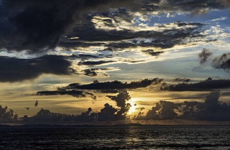 Mesmerizing view of Sunrise/Sunset at coastal region of remote tropical island. Dark Grey clouds and golden color due to sunlight adding more drama to the scene. Dispersion of light due to wavelength.