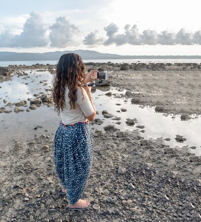 Trendy blogger in her 20s, with curly hairs wearing Patiala Salwar of Polka dots, an Ethnic Indian wear, is traveling solo and exploring the natural beauty of beach and clicking picture from cellphone Imagens - 144239973