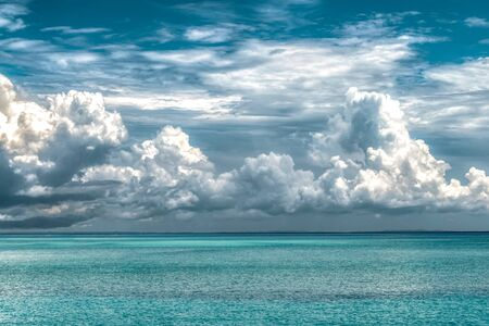 Calm ocean of turquoise color water and above it are huge dramatic cloud of type Cumulus during the onset of rainy season of monsoons; depicting the evaporation phase of Water cycle. Dream destination Imagens