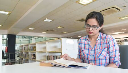 Young intelligent girl in her early 20s, studying in college library and preparing hard for upcoming semester exams. She is wearing eyeglasses, formal shirt with colorful checks. Imagens