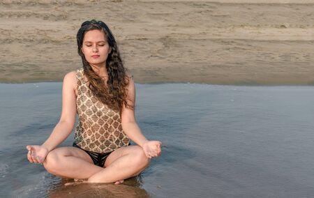 Gorgeous young girl in her early 20s, is meditating for her physical and mental well being, while sitting in lotus position on beach. Concept of health, yoga, well being, lifestyle, relaxation etc.. Imagens