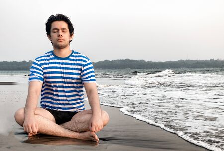 Handsome good looking boy in his early 20s, is meditating for physical and mental well being, while sitting in lotus position on beach. Concept of health, yoga, well being, lifestyle, relaxation etc.. Imagens