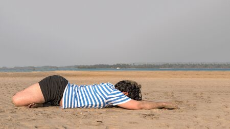 Side view photo of Young guy with fit body built practicing Yoga on beach in morning hours, by doing Forward bend Lotus position to keep his body flexible, relaxed and free from bone ailments. - Image