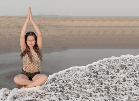 Beautiful photo of pretty young girl practicing yoga on beach in morning hours by raising both her hands up in prayer pose to relax her body, mind and soul while sitting in padmasana or lotus pose.