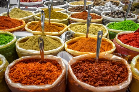 Colorful spices of many varieties stacked up for sale in traditional open air market of India. These spices are used as condiments, to flavor the food and is widely popular among foreign tourists. Imagens - 144924546