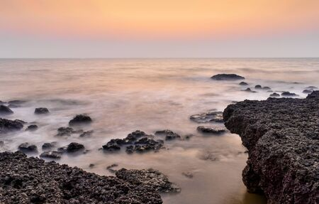 Amazing landscape comprising coastal Igneous rocks with clear visible horizon after sunset/ before sunrise. Sea waves crashing the rocks are smoothened by long exposure to give scene a milky effect. Imagens