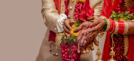 Very beautiful photo of a newly married Indian couple in ethnic attire offering flowers to God and taking blessings. Bride hands are decorated with henna design and colorful nuptial bangles. - Image. Imagens