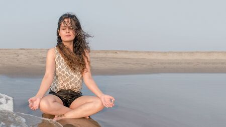 Beautiful brunette young girl in her early 20s is meditating in lotus position of yoga on an isolated beach for her physical and mental well-being. Concept of Health, Lifestyle, Yoga, Rejuvenation etc