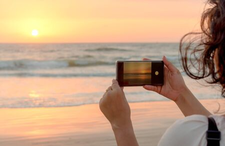 Beautiful side view photo of Young tourist girl exploring the world during vacations and is taking a sunset/sunrise shot in her smartphone. The photo to be clicked is visible in phone viewfinder. Imagens