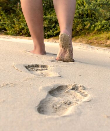 Beautiful Photo of footprints, foot impression on the beach sand while a barefooted girl with beautiful legs is walking on it. - Image. Concept of independence, lifestyle, beach walk, coastal etc. Imagens - 144959046