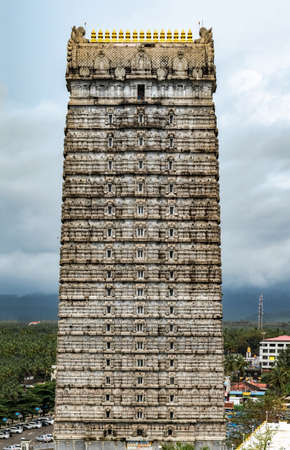 Magnificent 20-storeyed Gopuram at entrance of Lord Shiva Temple in Murdeshwara. Focus on top floors. This stone structure is constructed in traditional Dravidian architecture of Medieval South India. Editorial