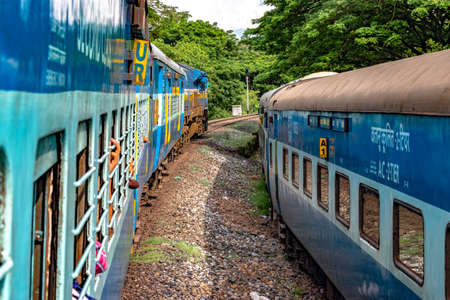 Indian Railways Train departing from station at slow pace, while crossing another train running parallel to it in opposite direction, amidst greenery of Western Ghats.