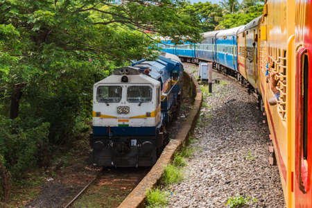 Two Trains of Indian Railways running parallel in opposite directions are crossing each other at slow pace, amidst hilly area of Western Ghats on a pleasant day. - Image Editorial