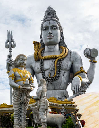 Hindu mythology Lord Shiva statue, meditating in Lotus Pose with Trident, drum in hand, snake around neck while ravana giving shivling to Brahmin boy in foreground.