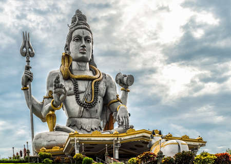 Magnificent and tall statue of Hindu mythology God, Lord Shiva in Murdeshwar, Karnataka, with snake coiled around his neck, while performing meditation and giving blessings and sermons to worshipers.